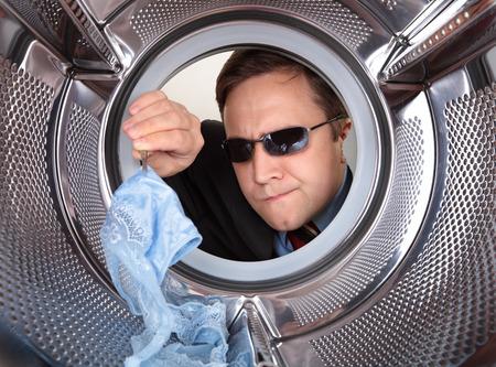 探偵は、汚れた服を洗濯機を検索します。 写真素材