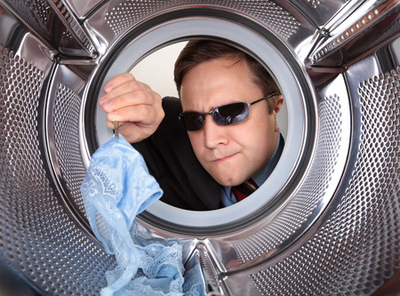 Detective searches through the dirty clothes in the washing machine Imagens