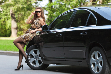 Sexy girl in a short dress is about the car in the summer the Park photo