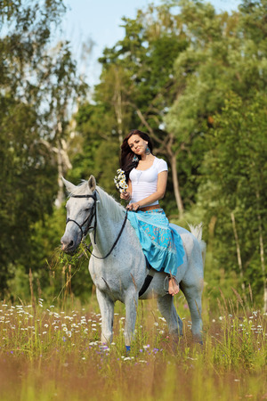 Young peasant woman rides a horse photo