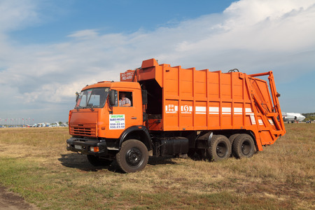 Orange garbage truck in the field Editorial