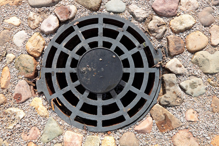 A round grille sewage wells to drain rain and melt water Stok Fotoğraf