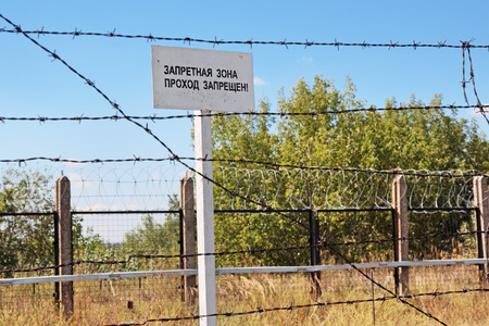 prison yard: Fence with barbed wire and warning plate with the inscription Forbidden zone in the Russian language