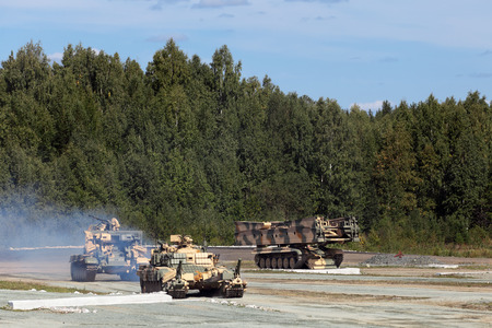 industrially: NIZHNY TAGIL, RUSSIA- AUG 23: Engineering military vehicles at the firing range - bridgelayer, demining machine and the machine mouldboard at the exhibition RUSSIAN DEFENCE EXPO 2012 on August, 23, 2012 at Nizhny Tagil, Russia