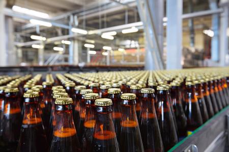 De voedingsindustrie. Glazen bierflesjes bewegen op transportband Stockfoto