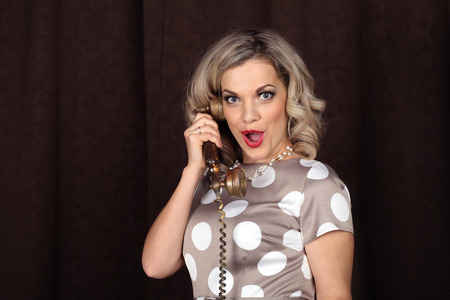 exultation: Surprised girl in the retro style of talking on the antique phone Stock Photo