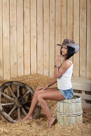barefoot cowboy: A young girl in cowboy hat sitting on a barrel in a barn with straw