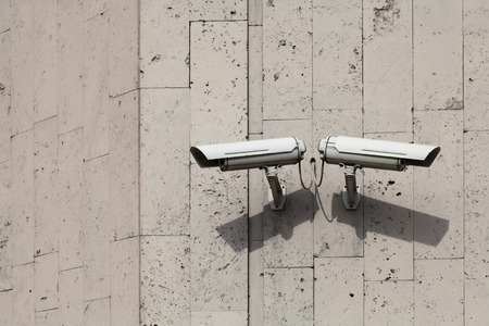 Two outdoor camera surveillance and control on the grey wall of the building photo