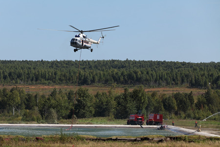 Fire helicopter draws up water from a fire reservoir for forest fire fighting