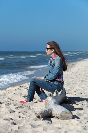 Thoughtful girl sits on the shore of the Baltic sea to the Curonian spit and looking afar