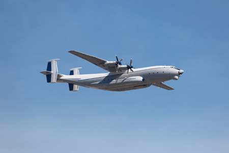 turboprop: A cargo turboprop aircraft flies on the background of blue sky