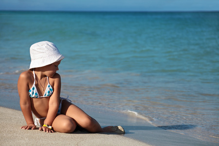 swimming costumes: Six-year-old girl in a bathing suit and boonie hat sits on the shore of the sea near the water