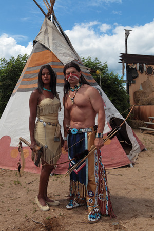 Indians man and woman stand against the background of teepee Stock Photo