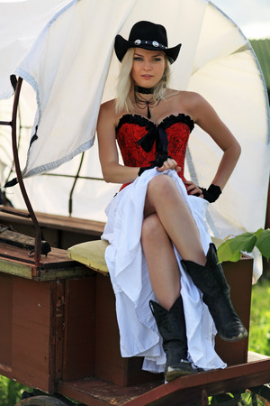 red corset: Sexy woman in red corset and a long white skirt sitting in the cart Stock Photo