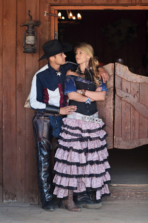 west: A man and a woman standing at the entrance of the saloon