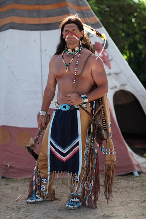 Indian stands about his teepee