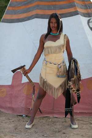 axe girl: Aggressive Indian girl with an axe and shield in hand against  the teepee