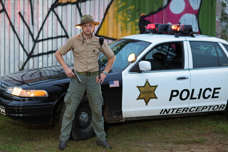 Policeman with a gun standing beside his car photo