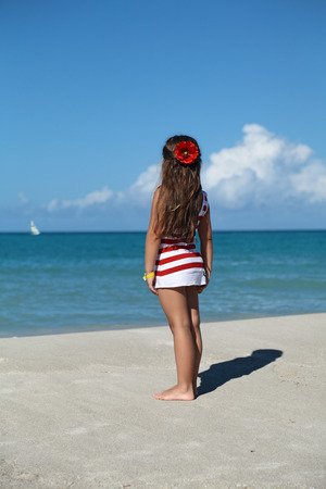 A little girl is standing at the seashore looking at the boat on the horizon photo