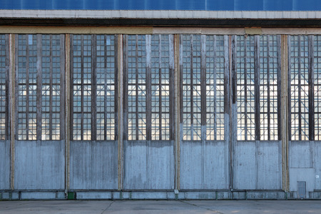 sectional door:  The huge gate of the assembly shop of the old aviation plant Stock Photo