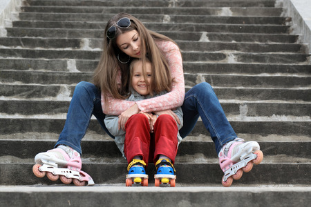 A young mother with her daughter sitting on the stairs in the Park with roller skates photo