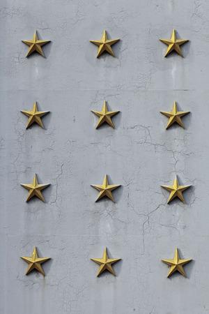 estrellas cinco puntas: Textura de metal pintado de color gris con estrellas amarillas de cinco puntas en la superficie