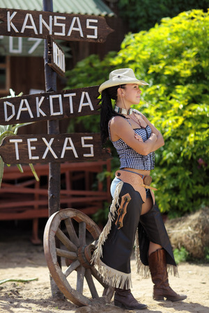 The girl in cowboy clothes standing near the road sign