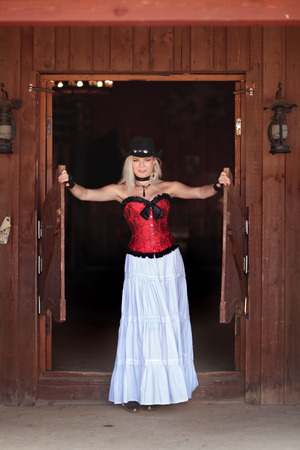 west: Sexy woman in red corset and a long white standing in the doorway of the old saloon  Stock Photo