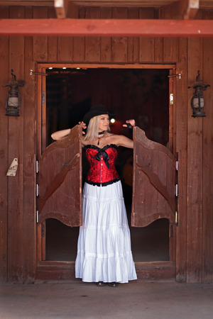Sexy woman in red corset and a long white standing in the doorway of the old bar