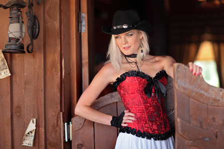 Sexy woman in red corset and a long white standing in the doorway of the old bar photo