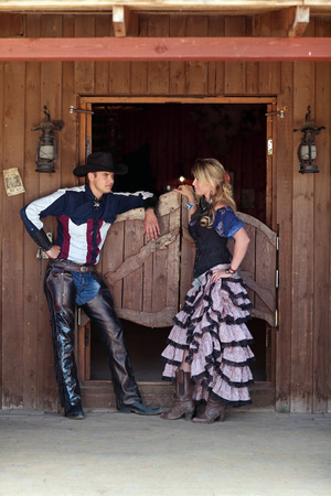 A man and a woman standing at the entrance of the saloon