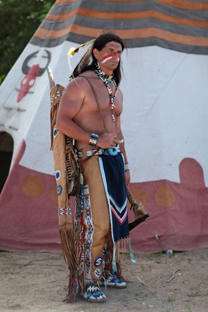 swarty: Indian stands about his teepee