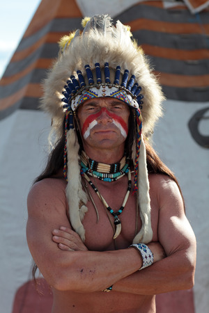 native american man: Portrait of an Indian on the background of the teepee Stock Photo
