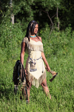Indian girl standing in the field and looks into the distance photo