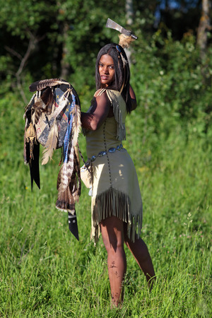axe girl: Aggressive Indian girl with an axe and shield in hand standing in the field