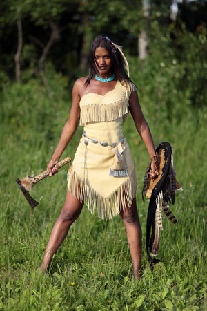 swarty: Aggressive Indian girl with an axe and shield in hand standing in the field