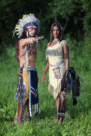 Indian chief with a young Indian on the green meadow photo