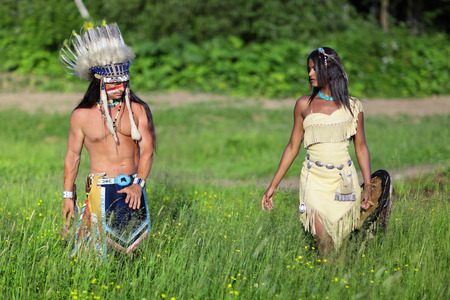 Indian chief with a young Indian go on the green meadow