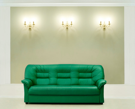 luxuriant: The green leather sofa, is put about a wall with candelabrums Stock Photo