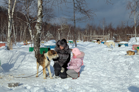 Mom and daughter stroking the dog in the kennel, Siberia, Russia photo