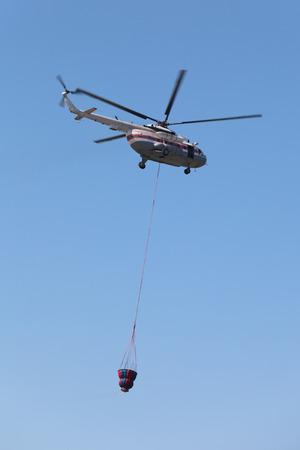Fire helicopter with the reservoir for water flies on the background of blue sky