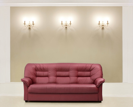 The red leather sofa, is put about a wall with candelabrums Stock Photo