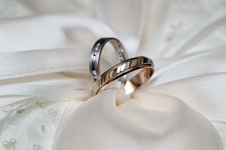 Two wedding rings from yellow gold lie on a dress of the bride Stock Photo