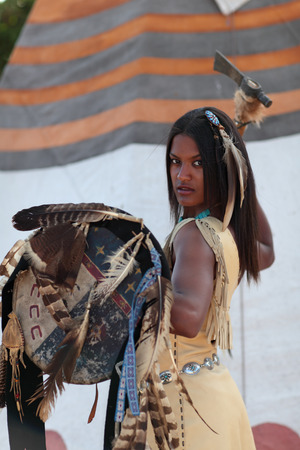 axe girl: Aggressive Indian girl with an axe and shield in hand against the background of the teepee Stock Photo