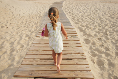 one little girl: The little girl goes on board road among sand