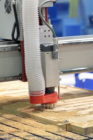 woodworker: Woodworker milling machine tool cuts out a pattern in a thick board