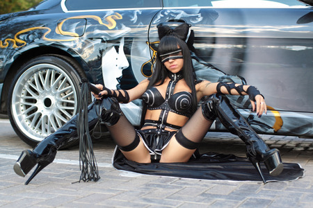 A young girl in sexy dress with a whip sits near the car Stock Photo