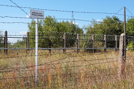 forbade: Fence with barbed wire and warning plate with the inscription Forbidden zone in the Russian language