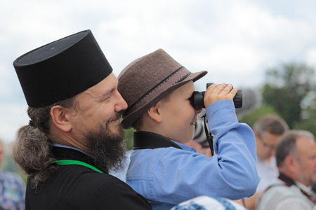 cleric: MOSCOW REGION, SERGIYEV POSAD, RUSSIA - JUL 18, 2014: The priest holds the child in her arms at the celebration of the 700th anniversary of the birthday of St. Sergius of Radonezh
