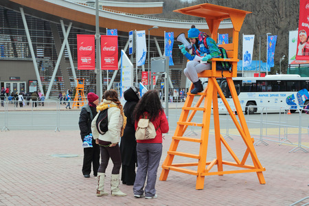 SOCHI, RUSSIA - MAR 14, 2014: Visitors consult with volunteer near the railway station Krasnaya Polyana, Sochi. Paralympics winter games 2014